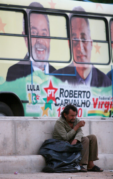 A street man sits on a curb near a poster for Brazilian President Luis Inacio Lula da Silva before a campaign rally in Belo Horizonte, capital of the southeastern state of Minas Gerais, Brazil, September 26, 2006. In spite of a series of corruption scandals which have stained his images, opinion polls show that Lula should win in the first round of the Oct. 1, 2006 election.(Australfoto/Douglas Engle)