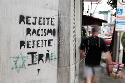 """A spray-painted sign reading """"Reject Racism Reject Iran"""" on a street in Sao Paulo, Brazil has been changed to read """"Reject Racism Reject Israel."""" A poll from 2011 showed both Israel and Iran as the two least popular countries among Brazilians and Latin Americans, paradoxically putting  the two countries, at odd on the world political scene, into the same categorty. For Latin Americans, they seem to be mirror reflections of each other. (Australfoto/Douglas Engle)"""