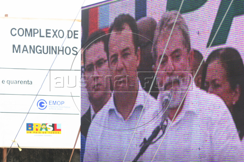 Brazilian President Luis Inacio Lula da Silva, right, and  Rio de Janeiro state Governor Sergio Cabral appear on a large screen during the inauguration of an ambitious slum development project in the Manguinhos slum of Rio de Janeiro, Brazil, Mar. 7, 2008.  Lula visited three slums where construction works, aimed at reducing crime, will begin on public transport, education, parks and in other areas. (Australfoto/Douglas Engle)