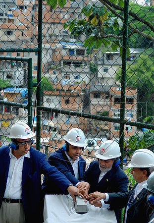 Brazilian President Luiz Inacio Lula da Silva, second from right, Rio de Janeiro's governor Sergio Cabral, second from left, vice-governor Luiz Fernando, left, and city's minister Marcio Fortes, right, press together the button to launch the works to build a lift to take uphill the residents of the Pavao/Pavaozinho slum complex, overlooking Ipanema beach, Rio de Janeiro, Brazil, Nov. 30, 2007. President Lula da Silva visited one of this city's most prominent slums to inaugurate the PAC, a multibillionnaire dollar work's program for the city's poor communities. (Australfoto/Renzo Gostoli)