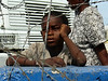 A boy watched Brazilian troops near their main base in Haiti. The Brazilian military, with 1,300 troops in the Caribbean nation, leads a force of 7,000 UN troops there since 2004. The mission is part of an effort by Brazil to take a larger role on the international stage - which some analysts say is a part of Brazil's desire for a seat on an eventual larger UN security council. Brazil has also accepted Palestinian refugees from Iraq. (Australfoto/Tom Phillips)<br /> STORY AVAILABLE