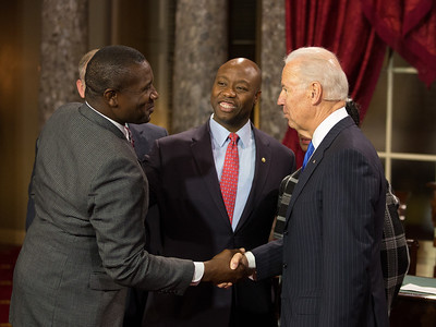 """If you need help on your pecs, let me know.""  Vice President Joe Biden (right) tells the large brother (left) of South Carolina Republican Senator Tim Scott. Sen. Scott (second left) participated in a mock swearing-in with his mother Frances Scott and Vice President Joe Biden. The ceremonial event took place in the Old Senate Chamber inside the U.S. Capitol Building in Washington D.C. on January 3, 2013. The official swearing-in ceremony happened earlier in the Senate chambers on the opening day of the 113th Congress. (Photo by Jeff Malet)."