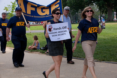 "The American Federation of Government Employees (AFGE) march to a rally to ""Save the American Dream"" on Capitol Hill in Washington DC on Thursday, July 28, 2011. ""In the past few days, it's become increasingly clear that congressional Republicans are willing to crash our entire economy just to keep tax breaks for millionaires, billionaires, corporate jet owners and oil companies,"" says the AFL-CIO. ""They're holding our economy hostage, but we still have the power to rise up and demand Congress raise the debt ceiling without a budget that savages working families."" Protest sign reads ""Hands Off Pensions, Medicare, Social Security"". (Photo by Jeff Malet)"