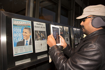 Sivaa of Chantilly VA was among the many pedestrians to stop to read and photograph the news about  President Obama's re-election in front of the Newseum in Washington D.C. on November 7, 2012. Front pages are displayed outside the Newseum on Pennsylvania Avenue, one from every state and the District of Columbia as well as a sampling of international newspapers. (Photo by Jeff Malet)
