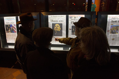 Pedestrians stop to read the news about  President Obama's re-election in front of the Newseum in Washington D.C. on November 7, 2012. Front pages are displayed outside the Newseum on Pennsylvania Avenue, one from every state and the District of Columbia as well as a sampling of international newspapers. (Photo by Jeff Malet)