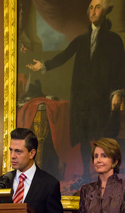 Mexican President-Elect Enrique Pena Nieto delivers brief remarks in the Rayburn Room at the U.S. Capitol building on November 27, 2012 in Washington, D.C. He appeared there with House Democratic Leader Nancy Pelosi (D-CA) (right in photo) and members of the Congressional Hispanic Caucus. In the background is a copy of the famous Lansdowne portrait by American artist Gilbert Stuart of George Washington, the first President of the United States. Pena Nieto's July election victory marked the return to power of the former ruling Institutional Revolutionary Party (PRI) after a 12-year absence. (Photo by Jeff Malet)