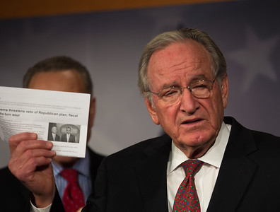 Sen. Tom Harkin holds news article indicating President Barack Obama will veto Republican tax plan.  Sen. Charles Schumer (D-NY), hidden left, and Sen. Tom Harkin (D-Iowa), right, hold a news conference at the Capitol in Washington D.C. on Wednesday, Dec. 19, 2012, to respond to Speaker John Boehner's (R-Ohio)  'plan B'  to avoid 'fiscal cliff' impending tax increases and budget cuts at the end of 2012 if Congress cannot reach a new budget agreement. (Photo by Jeff Malet)
