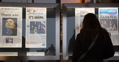 Pedestrians stop to read the news about  President Obama's reelection in front of the Newseum in Washington D.C. on November 7, 2012. Front pages are displayed outside the Newseum on Pennsylvania Avenue, one from every state and the District of Columbia as well as a sampling of international newspapers. (Photo by Jeff Malet)