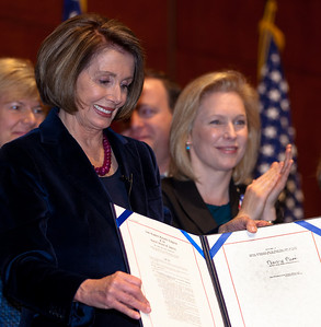 With members of the House and Senate and three discharged service members at her side, Speaker of the House Nancy Pelosi (D-CA) signed the repeal of Don't Ask, Don't Tell, Tuesday December 21, 2010 on Capitol Hill. In photo with Pelosi is Sen. Kirsten Gellibrand (D-NY). (Photo by Jeff Malet)