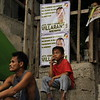 A boy is sitting in front of a campaign material of Romeo Villarante. The local bets of the Liberal Party (LP) visited the San Roque covered court last Thursday, April 4, 2013.