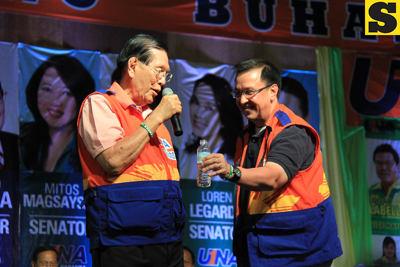 FATHER AND SON. Senatorial bet Jack Enrile gives a bottle of water to his father, Senate President Juan Ponce Enrile, during the proclamation rally of the United Nationalist Alliance (UNA) held at the Plaza Independencia, Cebu City on Tuesday, February 12, 2013. (Photo by Daryl D. Anunciado of Sunnex)
