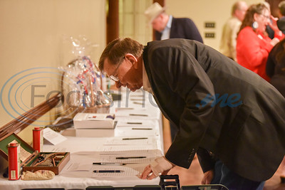 A guest makes a bid at a silent auction as part of the 2020 Republican Party President's Day Dinner in Jacksonville on Saturday, February 15.