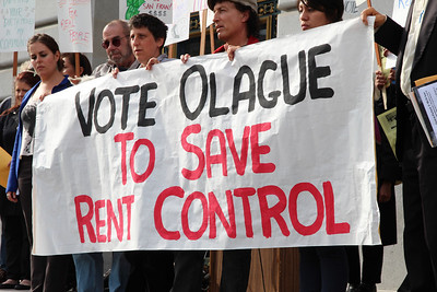 "Holding up the ""Vote Olague - To Save Rent Control"" sign, left to right, Ted Gullicksen, Sara Shortt, Tommi Avicolli Mecca and Maria Zamudio."