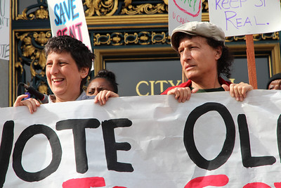 Holding up the sign, left to right, Sara Shortt and Tommi Avicolli Mecca.