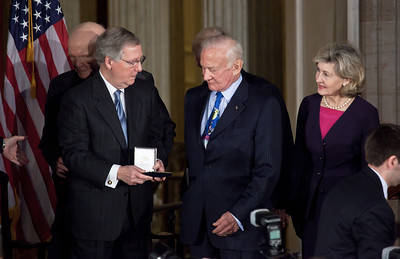 Senate Minority Leader Mitch McConnell (R-KY) presents gold medal to famous astronaut Buzz Aldrin. Senator Kay Bailey Hutchison (R-TX) stands on right. Space legends John Glenn, Neil Armstrong, Buzz Aldrin and Michael Collins were awarded Congressional Gold Medals, the nation's highest civilian honor, on Wednesday, November 16, 2011. The ceremony was held in the US Capitol Rotunda in Washington DC.  (Photo by Jeff Malet)