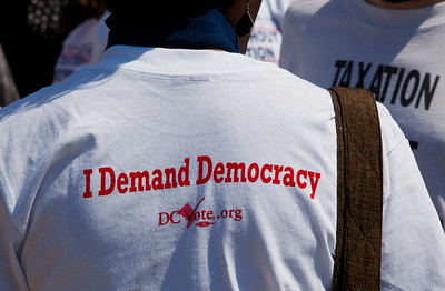 I Demand Democracy is the slogan of this DC Vote activist. DC shadow Senator Michael Brown was one of three arrested in an act of civil disobedience during a protest outside the Hart Senate Office Building on Capitol Hill in Washington DC on April 15, 2011. Brown joined a youth day Tax Protest targeting Senate Majority Leader Harry Reid (D-NV) who earlier in a budget deal with Republicans put restrictions on the District's ability to fund abortions providers. Also participating in the protest were DC Vote, an educational and advocacy organization dedicated to securing full voting representation in Congress and full democracy for the residents of the District of Columbia. (Photo by Jeff Malet)