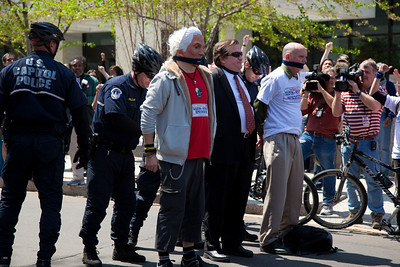 DC shadow Senator Michael Brown (center in black suit) was one of three arrested in an act of civil disobedience during a protest outside the Hart Senate Office Building on Capitol Hill in Washington DC on April 15, 2011. Brown joined a youth day Tax Protest targeting Senate Majority Leader Harry Reid (D-NV) who earlier in a budget deal with Republicans put restrictions on the District's ability to fund abortions providers. Also participating in the protest were DC Vote, an educational and advocacy organization dedicated to securing full voting representation in Congress and full democracy for the residents of the District of Columbia. Others arrested with Brown identified themselves as Adam Eidinger and Bob Johnsen. (Photo by Jeff Malet)