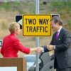 MassDevelopment announced on Tuesday a $1.85 million dollar investment for the the phase 4, the final phase, of Devens Jackson Road redevelopment project.  President & CEO of MassDevelopment Marty Jones and Matt Erskine Deputy Assistant Secretary of U.S. Commerce for Economic Development shack hands after hanging a two way  sign over the one way sign that will change that part of Jackson Road, during the event on Devens. SENTINEL & ENTERPRISE/JOHN LOVE