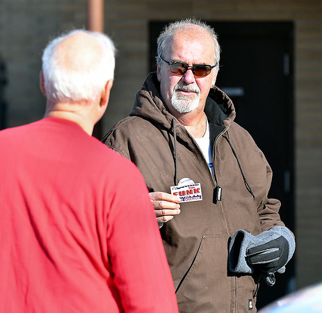 Tim Funk, right, Anderson City Council District 1 Democrat candidate, offers his card to a voter as he works the three precincts located at National Guard Armory Tuesday.