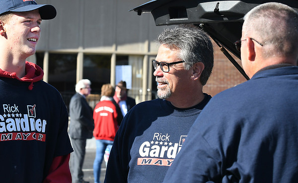 Republican candidate for Anderson Mayor Rick Gardner, center, talks with his supporters as his opponent, Thomas Broderick Jr., background, talks to his people as both candidates visit Ward 5, precinct 3 at St. Matthew Methodist Church at the same time Tuesday.