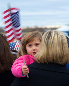 110312, Porthsmouth, NH - Chloe Bosma, 4, shows her support for presidential candidate Mitt Romney from her mother Kim's shoulder at a rally at Portsmouth International Airport on Saturday morning. Photo by Ryan Hutton