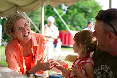 070312, Rutland, MA - Senatorial candidate Elizabeth Warren speaks with Ali Girard, 2, and her father Mark during a campagin stop at the Rutland Chicken BBQ for the town's 4th of July celebrations. Herald photo by Ryan Hutton