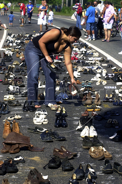 A woman arrange 600 pair of shoes of violence's victimes in Flamengo Park, Rio  de Janeiro, Brazil, Jul. 06, 2003.  Authorities in Rio de Janeiro bulldozed and burned almost 5000 fire arms confiscated betwen 1997 and 1998. (Austral Foto/Renzo Gostoli)