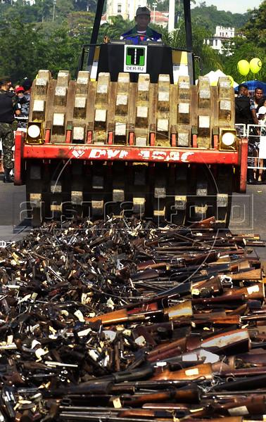 A bulldozer destroys more 4000 fire arms in Flamengo,  Rio  de Janeiro, Brazil, Jul. 06, 2003.  Authorities in Rio de Janeiro bulldozed and burned almost 5000 fire arms confiscated betwen 1997 and 1998. (Austral Foto/Renzo Gostoli)