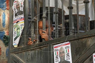 A boy looks through the gate of a school, which is a polling station in Port au Prince, Haiti, Nov. 26, 2010, but which also is a refugee camp for victims of the Jan. 2010 earthquake.(Australfoto/Douglas Engle)