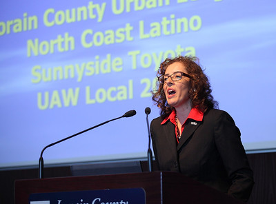Lilleanna Cavanaugh, Exec, Director for the Ohio Commission on Hispanic/Latino Affairs peaks about opening doors at the 19th Annual Hispanic Leadership Conference while the names of event sponsors are displayed behind her. photo by Ray Riedel