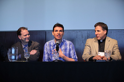 Andres Useche, award winning writer, director, artist, signer-songwriter and activist speaks during the Immigration Forum at the 19th Annual Hispanic Leadership Conference. he is flanked by Richard Herman, immigration Lawyer on the left, and Fr. Bill Thaden, pastor of Sacred Heart Parish on the right. photo by Ray Riedel