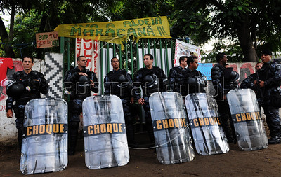 Riot police officers stand guard at the entrance of the old indigenous museum --aka Aldea Maracana-- next to Maracana stadium in Rio de Janeiro, Brazil, January 12, 2013.  Indians of about 10 ethnicities — mostly Guarani, Pataxo, Kaingangue and Guajajara- have been occupying the place since 2006 as a protest against Rio de Janeiro's governmet decision to throw them out and pull down the building to construct 10,500 parking lots for the upcoming Brazil 2014 FIFA World Cup. (Austral Foto/Renzo Gostoli)