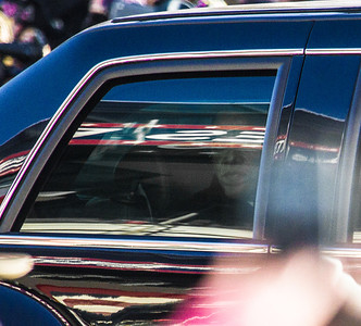 Partially hidden by a tinted window, the darkened visage of President Barack Obama peers from his limo in the Presidential Inauguration Parade in Washington, District of Columbia, Jan. 21, 2013, along Pennsylvania Avenue from the U.S. Capitol to the White House. (Photo by Jeff Malet)