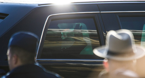 Partially hidden by a tinted window, the darkened visage of a waving President Barack Obama peers from his limo in the Presidential Inauguration Parade in Washington, District of Columbia, Jan. 21, 2013, along Pennsylvania Avenue from the U.S. Capitol to the White House. (Photo by Jeff Malet)