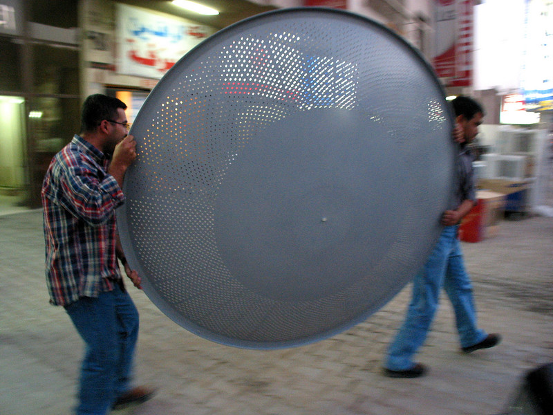 Iraqis carry a satellite television antenna to their car in Baghdad, Iraq. Banned during the rule of Saddam Hussein, the dishes are selling quickly as Iraqis satisfy their appetite for information and pop culture. Viewers say they like to watch music videos mostly, but Arabic language Egyptian soap operas also are a big hit.(Australfoto/Douglas Engle)
