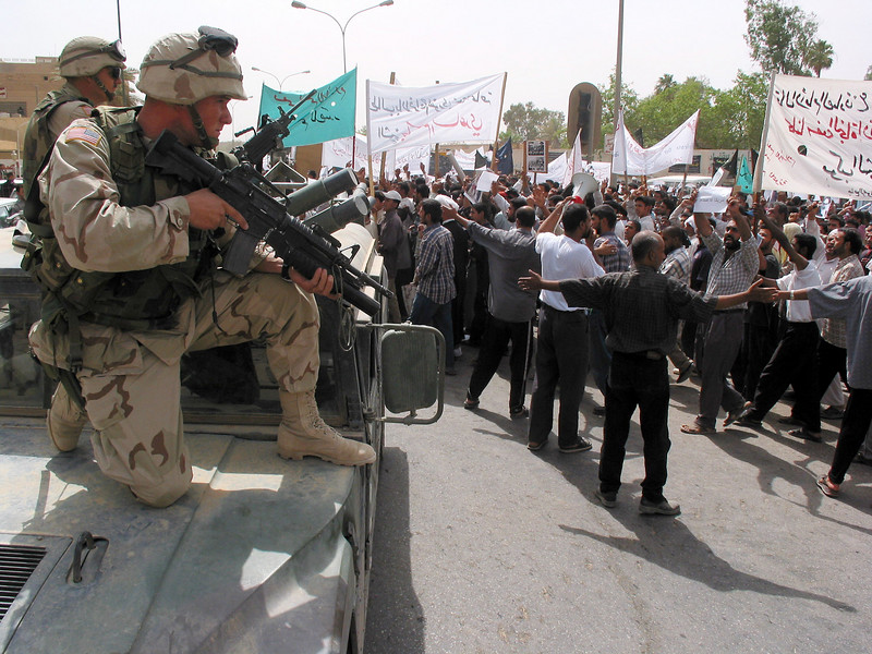 American soldiers stand ready as protestors demand the release of Islamic Shiite religious leader Jassim Al Saedi, in custody of US troops, in Baghdad, Iraq. The US military is finding that invading a nation is easier than ruling it.(Australfoto/Douglas Engle)