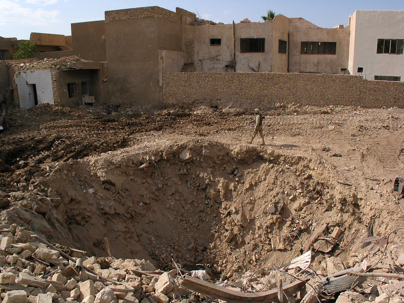 An American soldier walks past a bomb crater in Baghdad, Iraq. A bomb struck a restaurant April 7, 2003 in an attempt to kill Saddam Hussein, whose wherabouts are still not known. The US military is currently excavating the site for any clues.(Australfoto/Douglas Engle)