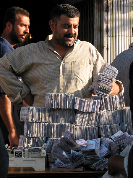 A man waits to change Iraqi Dinars at a streetside table in Baghdad, Iraq. The currency, which bears the portrait of Saddam Hussein fluctuates greatly in the post-war economy.(Australfoto/Douglas Engle)