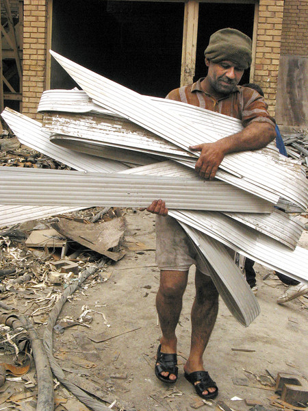A man carries scrap metal from the bomb-damaged electric company building in Baghdad, Iraq. Iraquis, trying to continue with their lives after Saddam Hussein, are trying to salvage what they can from damaged buildings.(Australfoto/Douglas Engle)