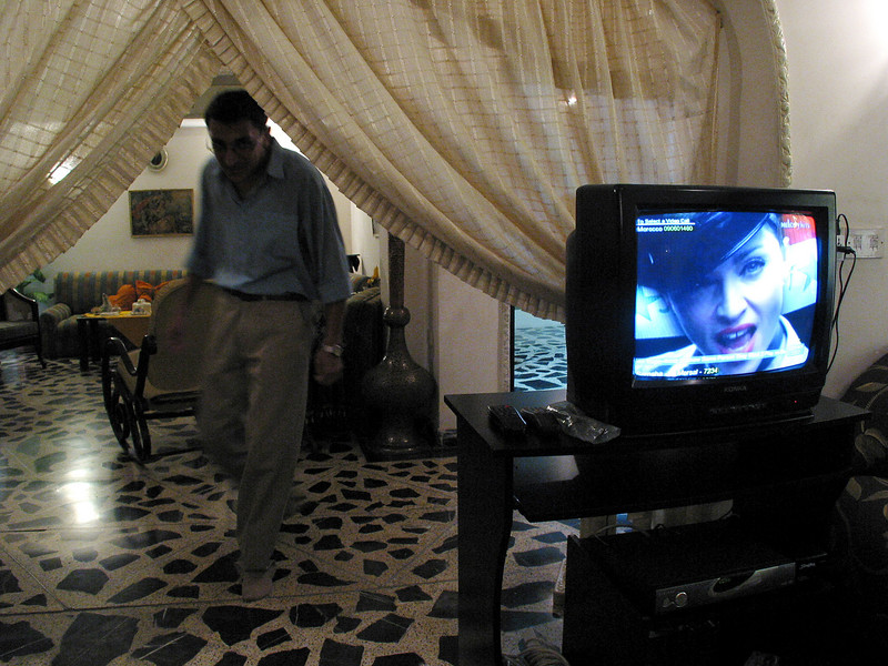 Iraqi Ali Hassan Zaki, 21 walks past a Madonna video playing on his television with a satellite antenna in Baghdad, Iraq. Banned during the rule of Saddam Hussein, the dishes are selling quickly as Iraqis satisfy their appetite for information and pop culture. Viewers say they like to watch music videos mostly, but Arabic language Egyptian soap operas also are a big hit.(Australfoto/Douglas Engle)