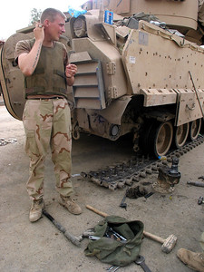 A US soldier near a broken Bradley armored vehicle in Baghdad, Iraq. The US military is finding that governing a nation is much more work than taking it over.(Australfoto/Douglas Engle)
