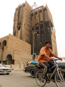 Traffic circulates past the bomb-damaged electric company building in Baghdad, Iraq. (Australfoto/Douglas Engle)