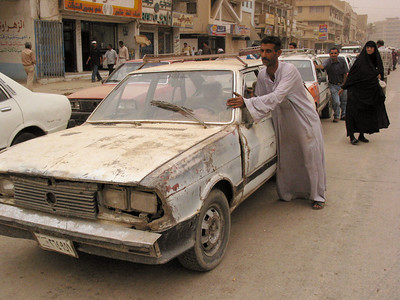 A man pushes his car in the line for the gas station in Baghdad, Iraq. While Iraq has lots of oil, power outtages have cut back the refining porcess, causing shortages.(Australfoto/Douglas Engle)