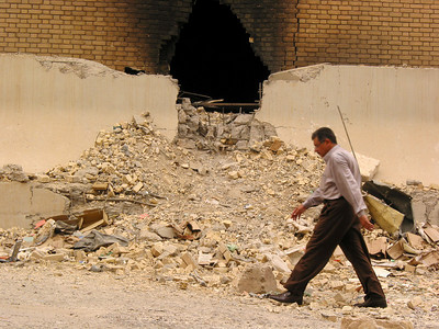 A man walks past the bomb-damaged electric company building in Baghdad, Iraq. (Australfoto/Douglas Engle)