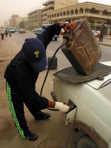A gasoline vendor fills a car's tank in Baghdad, Iraq. While Iraq has lots of oil, power outtages have cut back the refining porcess, causing shortages.(Australfoto/Douglas Engle)