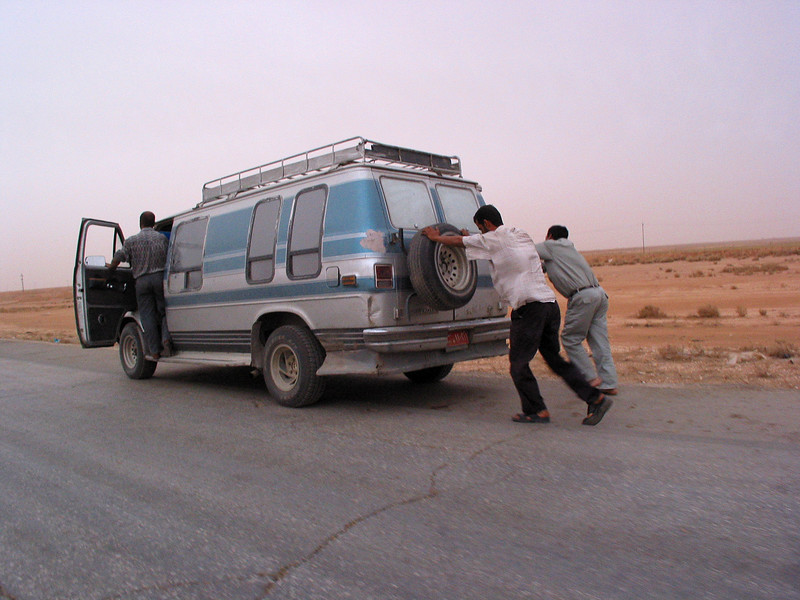 Men push a car across no-man's land from Jordan to the Iraqi border station. While Iraq has lots of oil, power outtages have cut back the refining porcess, causing shortages.(Australfoto/Douglas Engle)