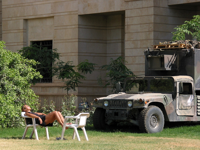 A female American soldier takes a sunbath on the lawn of a building in a palace complex in Baghdad, Iraq. The complex, off limits to Iraqis during the time of Saddam Hussein, has now been taken over by American forces, who use it as an administrative base.(Australfoto/Douglas Engle)