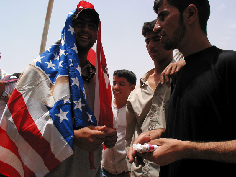 A man wears and American flag to protect from the sun in the Arab style  in Baghdad, Iraq.(Australfoto/Douglas Engle)
