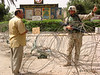 A US soldier gives a man directions from behind razor wire in Baghdad, Iraq.(Australfoto/Douglas Engle)