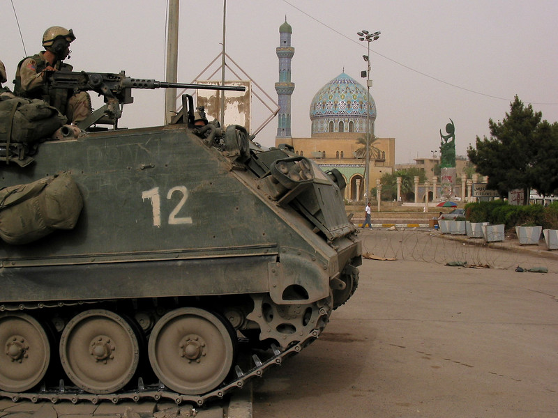 A US armored vehicle drives past a mosque in Baghdad, Iraq. The US military is finding that governing a nation is much more work than taking it over. (Australfoto/Douglas Engle)
